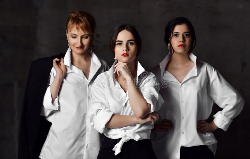 Lag av brutala tre och stilfull kvinna i vita mäns skjortor som poserar som affischen av filmen arkivbilder