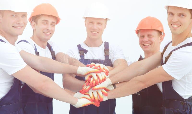 Lag av byggmästare som står med händer som tillsammans knäppas fast arkivfoto