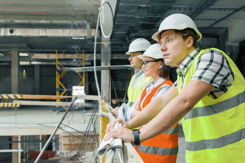 Lag av byggmästare, teknikerer, arkitekter på konstruktionsplatsen, kopieringsutrymme Konstruktions-, utvecklings-, teamwork- och arkivfoton