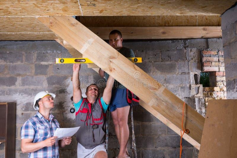 Lag av byggnadsarbetare som bygger trappuppgången arkivfoto