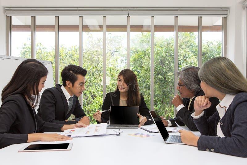 Lag av den asiatiska affären som poserar i mötesrum Funktionsduglig brainstor royaltyfri bild