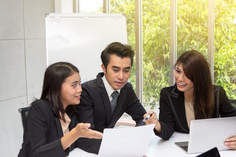 Lag av den asiatiska affären som poserar i mötesrum Funktionsduglig brainstor royaltyfri foto