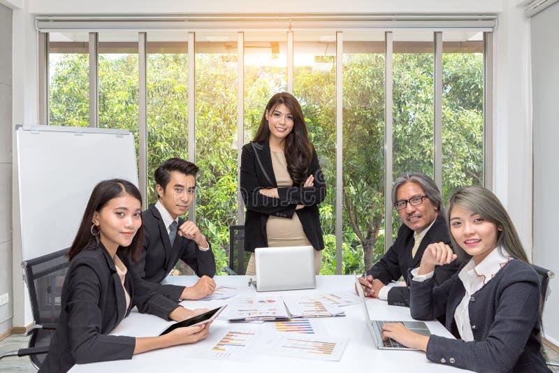 Lag av den asiatiska affären som poserar i mötesrum Funktionsduglig idékläckning på rymligt bräderum på kontoret Framstickande so royaltyfri fotografi