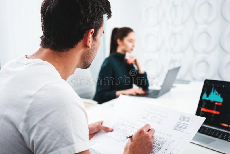 Lag av den manliga och kvinnliga arkitektformgivaren i regeringsställning som arbetar på anteckningsboken och byggande ritning royaltyfri foto
