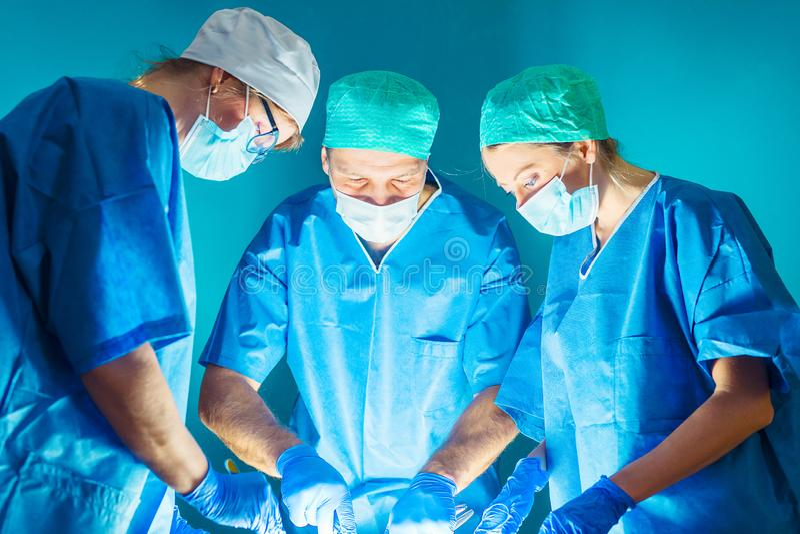 Lag av doktorer som arbetar under kirurgi arkivbild