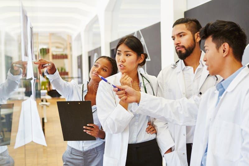 Lag av doktorer som diskuterar röntgenstrålebild arkivfoton