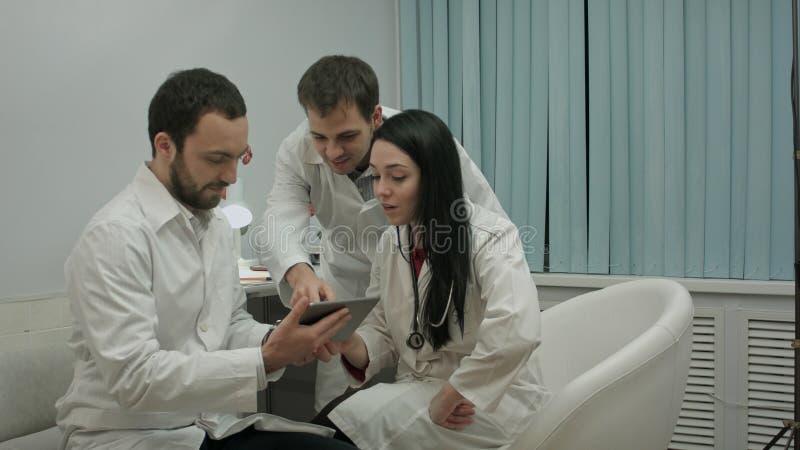 Lag av doktorer som håller ögonen på något som är rolig på minnestavlaPC i ett medicinskt kontor royaltyfria bilder