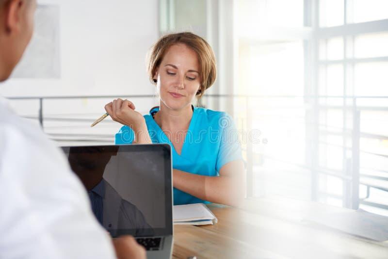 Lag av doktorn och sjuksköterskan som diskuterar ett tålmodigt diagnossammanträde på skrivbordet i ljust modernt kontor royaltyfria bilder