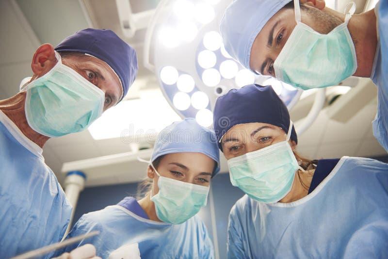 Lag av kirurger ?ver operationsbordet royaltyfri foto