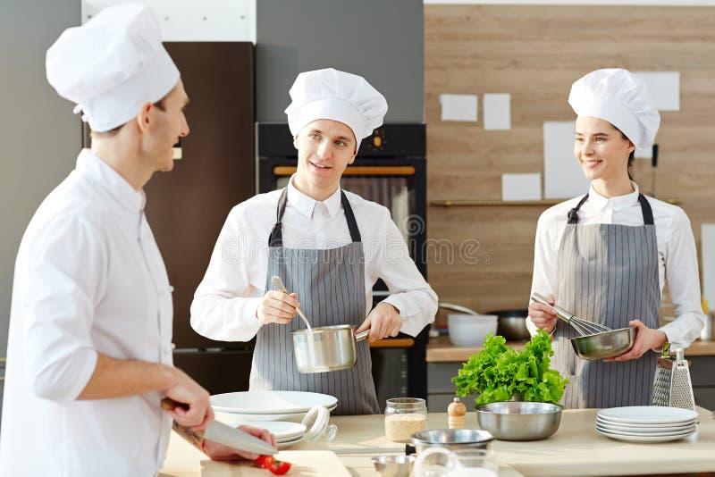 Lag av kockar som talar på arbete royaltyfria foton