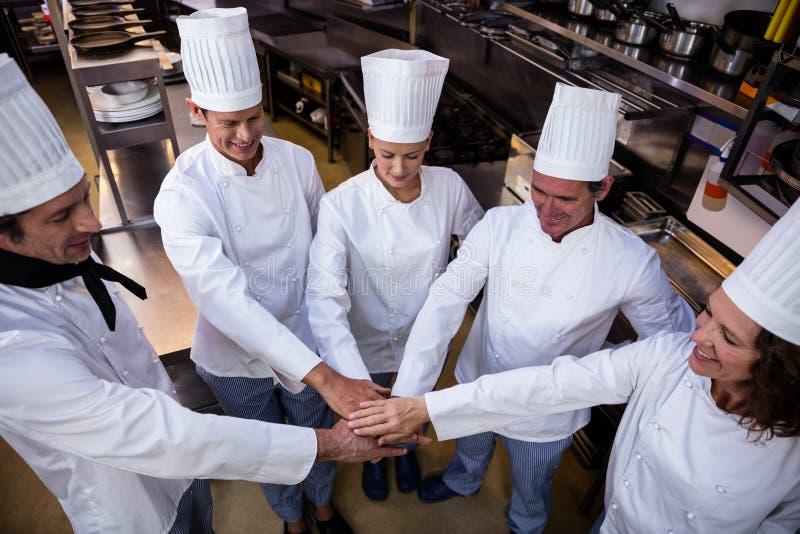 Lag av kockar som tillsammans sätter händer royaltyfri fotografi