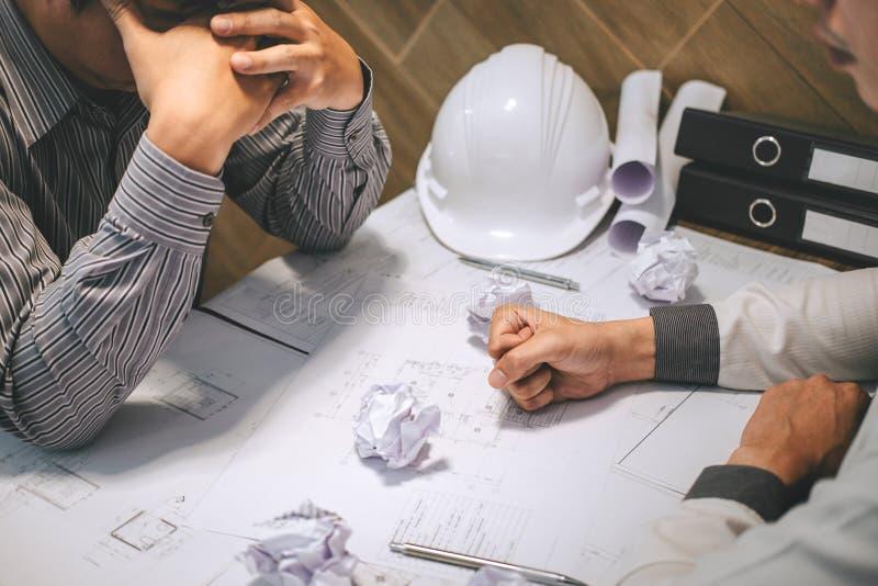 Lag av konstruktionsteknik eller arkitektpartner att diskutera en ritning, medan kontrollera information på att dra och att skiss arkivfoton