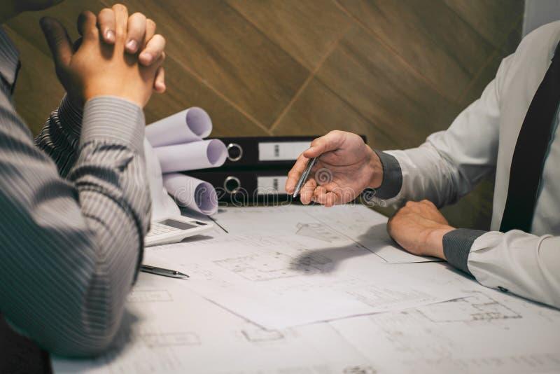Lag av konstruktionsteknik eller arkitektpartner att diskutera en ritning, medan kontrollera information på att dra och att skiss fotografering för bildbyråer