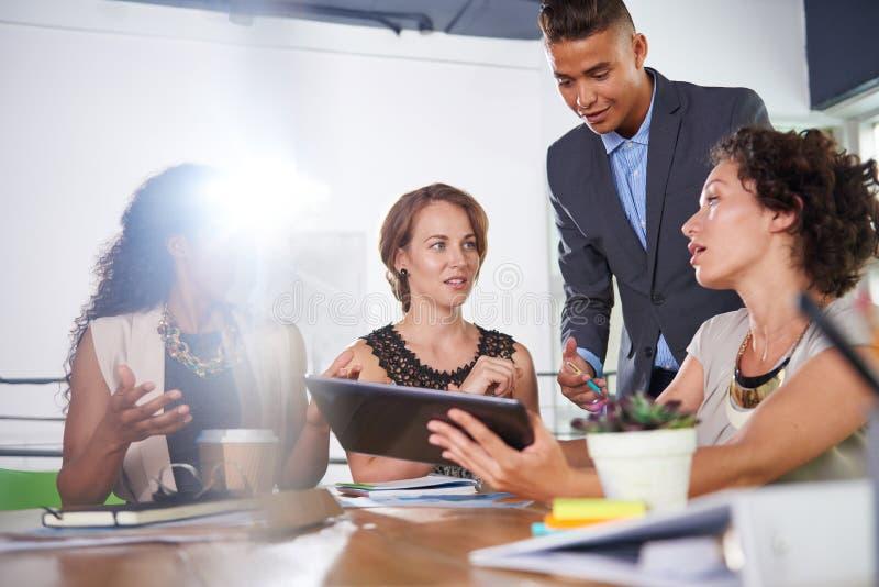 Lag av lyckat affärsfolk som har ett möte i utövande solbelyst kontor arkivbilder