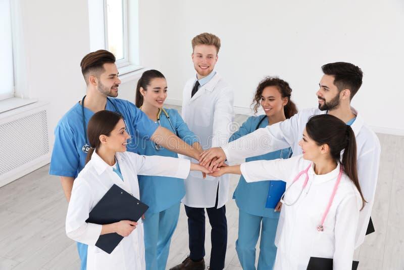 Lag av medicinska arbetare som tillsammans rymmer händer i sjukhus arkivfoto
