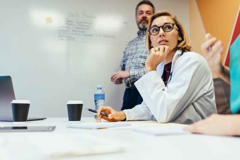 Lag av medicinska professionell som möter i styrelse arkivbild