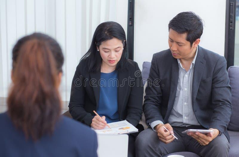 Lag av personer för affär som tre tillsammans arbetar på en bärbar dator med under ett möte royaltyfri bild