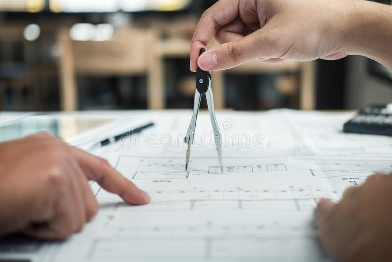 Lag av teknik- eller arkitektmötet och att diskutera på ritning och byggande modell, medan kontrollera information på att skissa royaltyfri bild