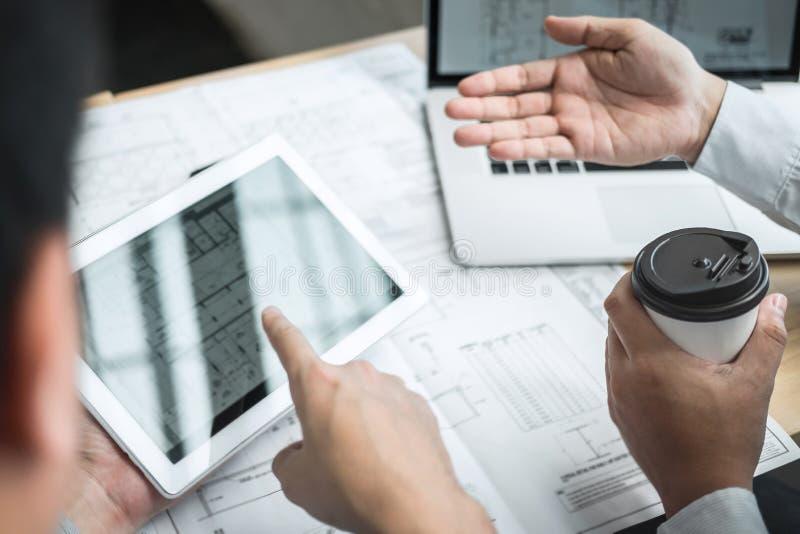 Lag av teknik- eller arkitektmötet och att diskutera på ritning och byggande modell, medan kontrollera information på att skissa royaltyfria foton