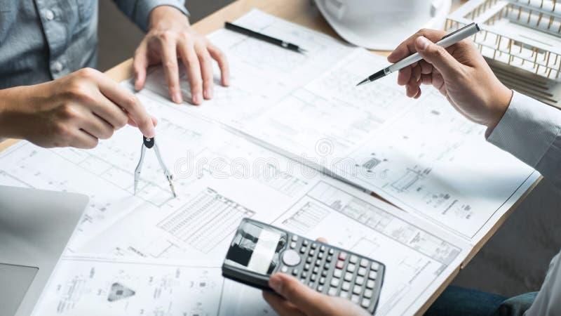Lag av teknik- eller arkitektmötet och att diskutera på ritning och byggande modell, medan kontrollera information på att skissa royaltyfri foto