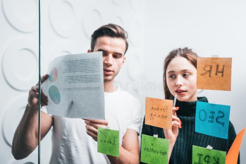 Lag av timme-chefer som diskuterar ny strategi av affärsanseendet bak den klibbiga exponeringsglasanmärkningsväggen på kontoret arkivfoton