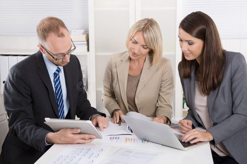 Lag av tre affärspersoner som tillsammans sitter på skrivbordet i ett möte arkivbild