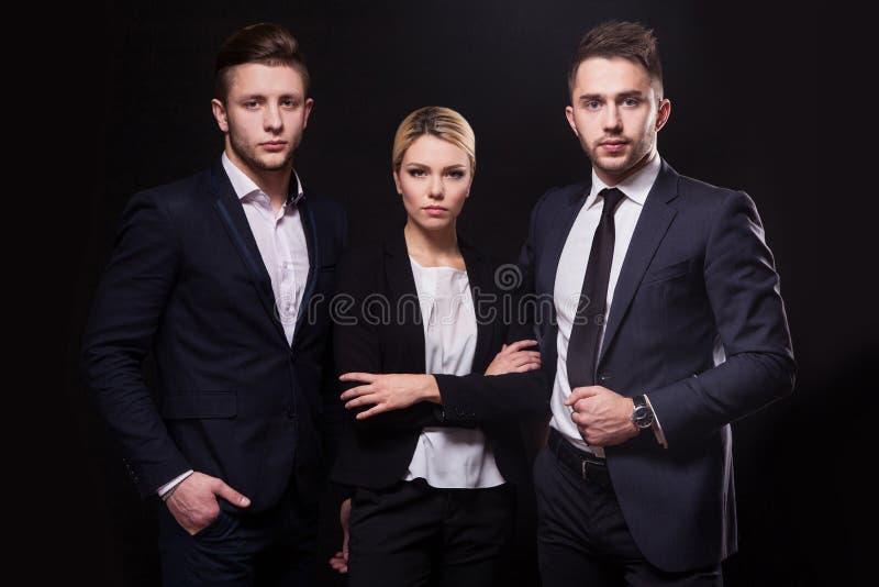 Lag av tre lyckade stilfulla unga advokater på en svart backgr royaltyfri foto