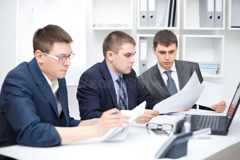Lag av unga affärsmän som gör någon skrivbordsarbete royaltyfri bild