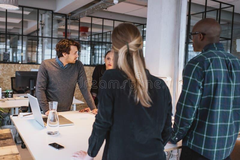 Lag av unga formgivare som tillsammans i regeringsställning arbetar royaltyfri bild
