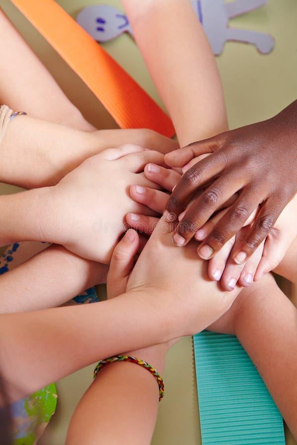 Lag av ungar som staplar deras händer royaltyfria foton