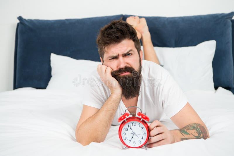 Lag de Hipster gebaarde mens in bed met wekker Tijd te ontwaken Waarom u elke ochtend vroeg zou moeten wekken gezondheid royalty-vrije stock foto