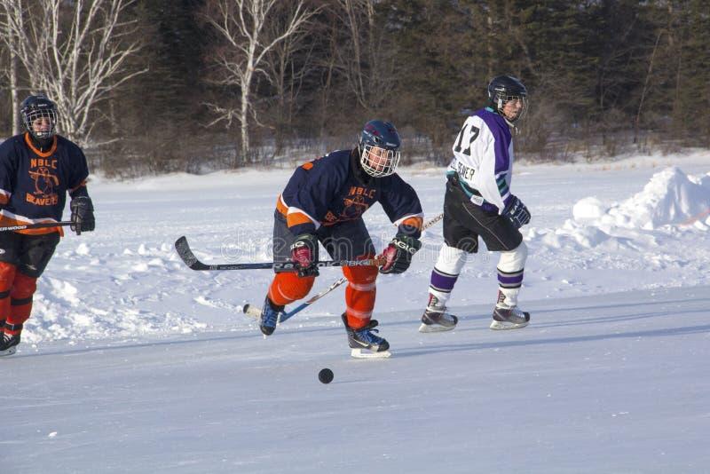 Lag för kvinna` s konkurrerar i en dammhockeyfestival i Rangeley royaltyfri bild