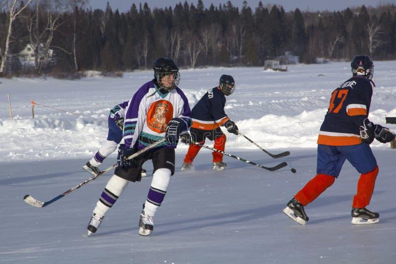 Lag för kvinna` s konkurrerar i en dammhockeyfestival i Rangeley arkivbild