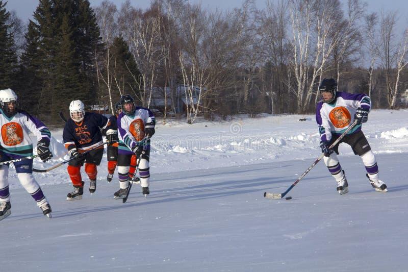 Lag för kvinna` s konkurrerar i en dammhockeyfestival i Rangeley arkivfoton