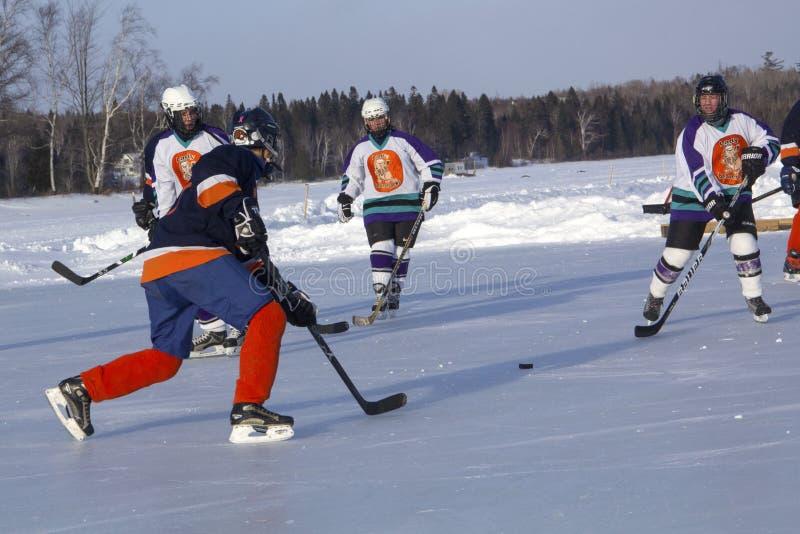 Lag för kvinna` s konkurrerar i en dammhockeyfestival i Rangeley arkivbilder