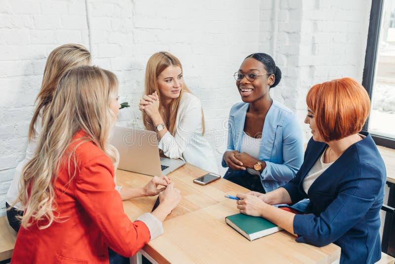 Lag för unga kvinnor upp med frilans- vänner och att skapa en liten coworking klubba royaltyfri bild