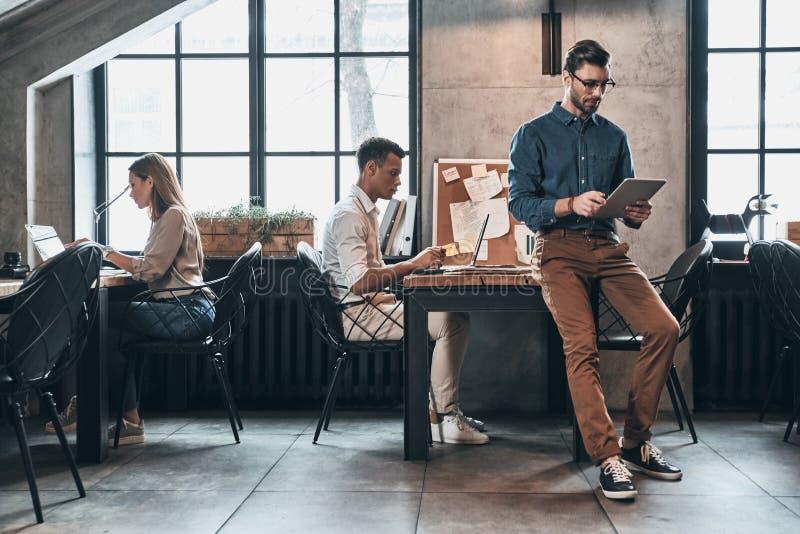 Lag på arbete Ungt modernt folk i smart concentra för tillfälliga kläder royaltyfria foton