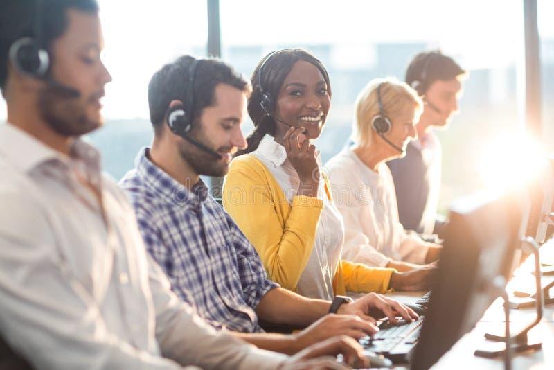 Lag som arbetar på datoren med hörlurar med mikrofon royaltyfria foton