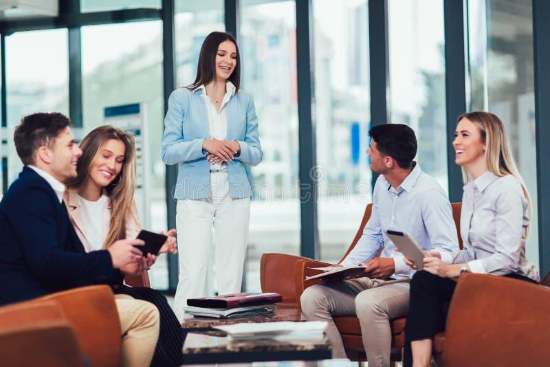 Lag som arbetar på nytt projekt och le Man och kvinnor som tillsammans sitter i det moderna kontoret f?r projektdiskussion arkivfoton