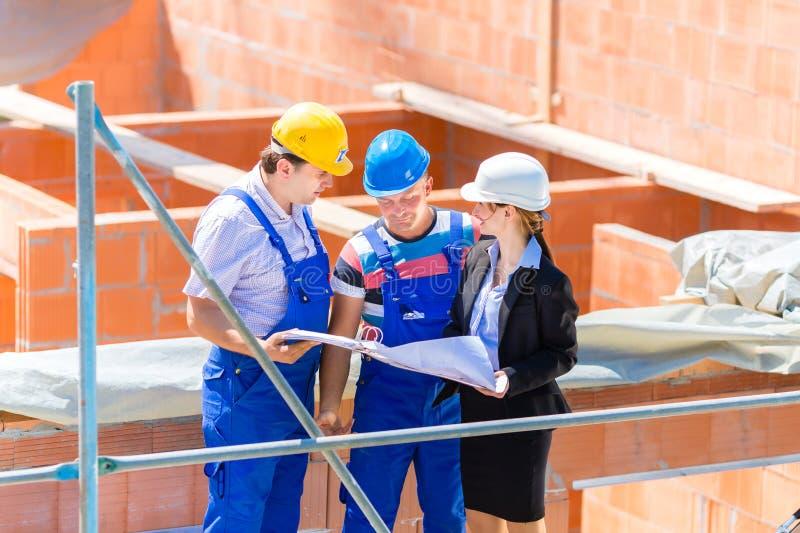 Lag som diskuterar konstruktions- eller byggnadsplatsplan arkivbilder
