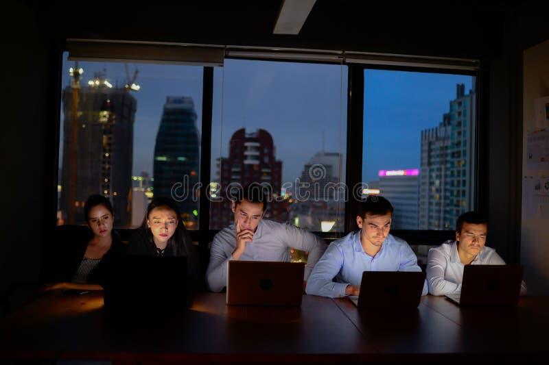 Lag som tre arbetar med datorövertid på natten och lågt ljus royaltyfri bild
