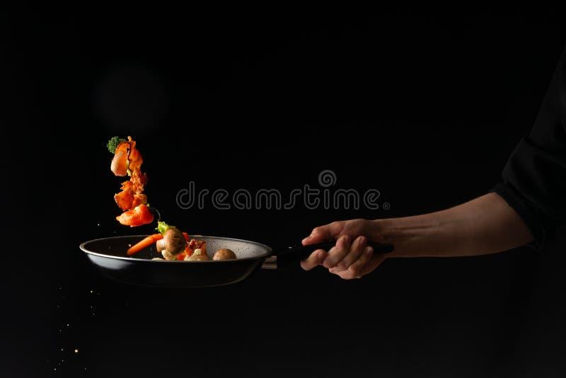 Laga mat att f?rbereda baconskivor med vitl?k och varm peppar och broccoli i en panna arkivfoto