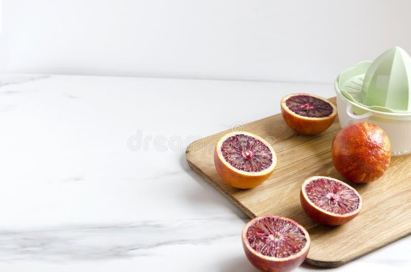 Laga mat av ny läcker blodapelsinfruktsaft Manuell juicer och skärbräda T?m utrymme f?r din design royaltyfri bild
