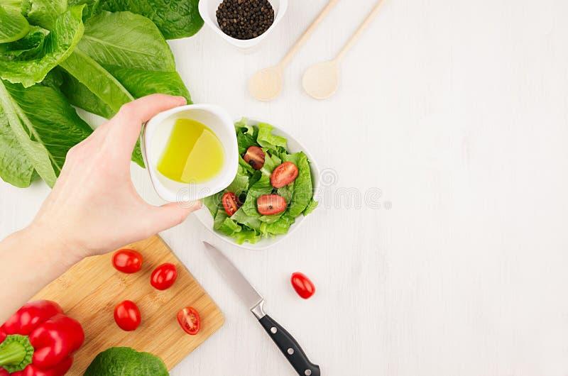 Laga mat banta rå sund sallad - olivoljaflöde ner på ny grön sallad med tomater i bunke, ingredienser på mjuk vit uppvaktar royaltyfri bild
