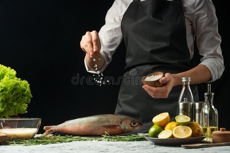 Laga mat chefen av ny fisk, saltar kocken fisken på en svart bakgrund med citroner, limefrukter fotografering för bildbyråer