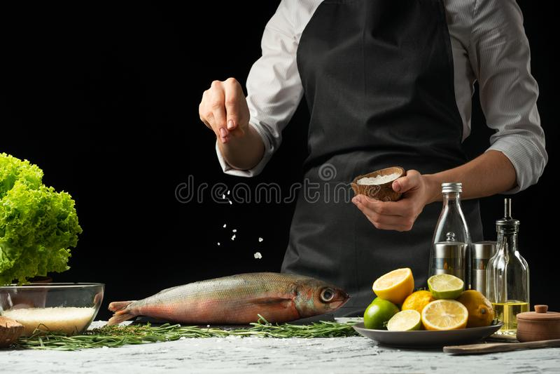 Laga mat chefen av ny fisk, saltar kocken fisken på en svart bakgrund med citroner, limefrukter royaltyfri bild