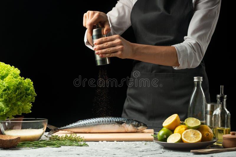 laga mat chefen av ny fisk, strilar kocken den krydda fisken på en svart bakgrund med citroner, limefrukter, rosmarin och thym royaltyfria foton