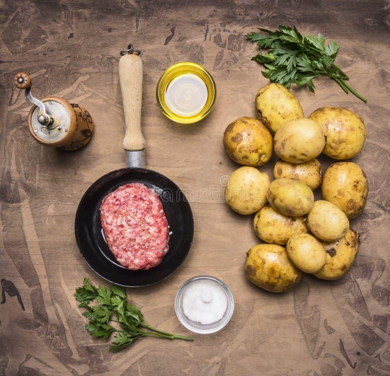 Laga mat den hemlagade hamburgaren med småfiskar, persilja och kryddor, nötköttfilé i en liten panna, trälantligt slut för bästa  arkivbilder