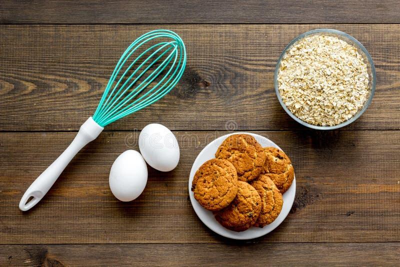 Laga mat det hemmastadda begreppet för kakor Ingredienser och instrument för gör kakor Nya kakor nära mjöl, ägg och att vifta på royaltyfria foton