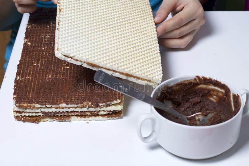 Laga mat dillandekakan En kvinna sätter en bunt av rånkakor, suddig med en blandning av kakao och smör Växelvis med rånkakor arkivfoto